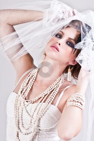 Attractive Young Woman Wearing a Veil stock photo, Attractive young woman wearing a veil, a pearl necklace and a bracelet. Vertical shot. by Angela Hawkey