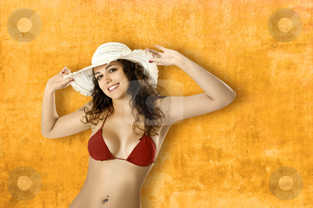 Summer woman stock photo, Portrait of a beautiful young woman in bikini posing in front of a yellow wall by ikostudio