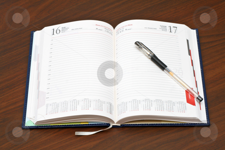 Diary stock photo, Diary and a pen on wooden table by Jan Remisiewicz