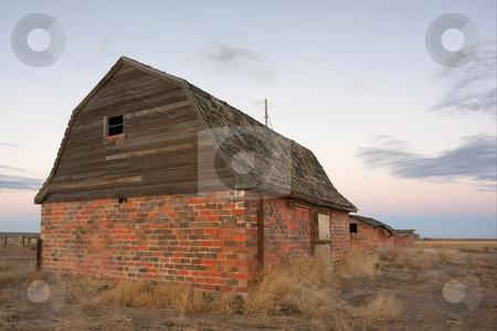 Abandoned farm buildings in prairie stock photo, Abandoned brick barn and farm buildings in eastern Colorado prairie at dusk by Marek Uliasz