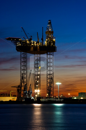 Big drilling platform in dock stock photo, Big drilling platform in repair in the harbour at sunset by Colette Planken-Kooij