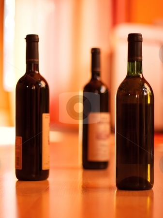 Wine Bottles stock photo, Three bottles of wine on the floor of a bright room (only one in focus, smooth soft image) by P?