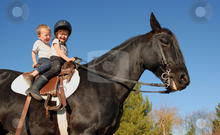 Children on stallion stock photo, Two happy children on their black stallion by Bonzami Emmanuelle
