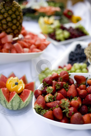 Table of Food stock photo, A table of food with strawberries, grapes, pineapple, watermellon, and an orange in the foreground. by Daniel Vineyard