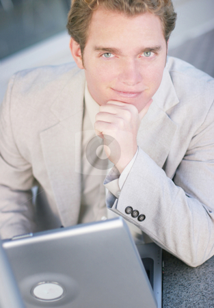 Confident business man stock photo, A confident business man sitting at a table with his laptop and his hand on his chin by Daniel Vineyard