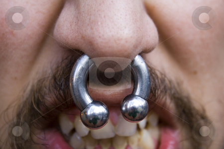 Silver septum ring facial piercing stock photo, A close up of a man's silver septum ring facial piercing by Derek Neuland