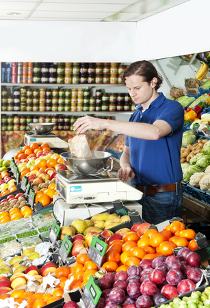 Weighing fresh fruits stock photo, Greengrocer weighing fresh food on a digital scale by Corepics VOF