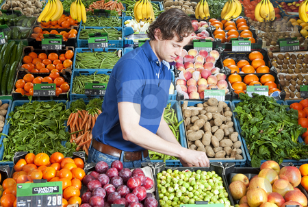 Greengrocer at work stock photo, A greengrocer at work amidst various crates of fresh fruit and vegetables in a shop by Corepics VOF