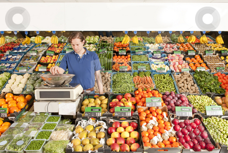 Greengrocer at work stock photo, A green grocer weighing vegetables in a grocery shop by Corepics VOF