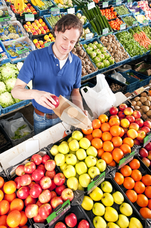 Greengrocer stock photo, Green grocer putting red apples in a brown paper bag by Corepics VOF