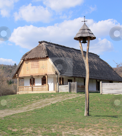 Bell stock photo, Rural thatched roof houses and a bell. by Gall&oacute; Guszt&aacute;v