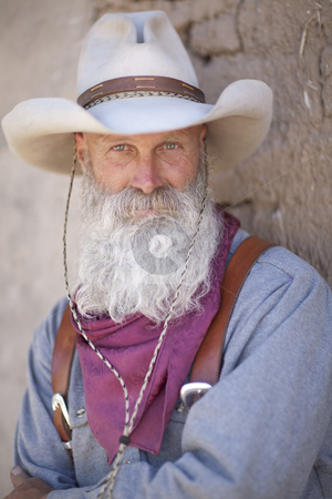 Cowboy With a Long White Beard stock photo, Portrait of a cowboy wearing a tall hat and sporting a long white beard. He is dressed in a heavy work shirt and kerchief. Vertical shot. by Dan Bannister