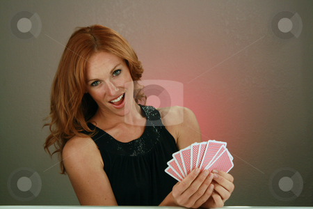 Beautiful Redhead with Playing Cards (5) stock photo, A lovely redhead model holds a hand of playing cards. by Carl Stewart