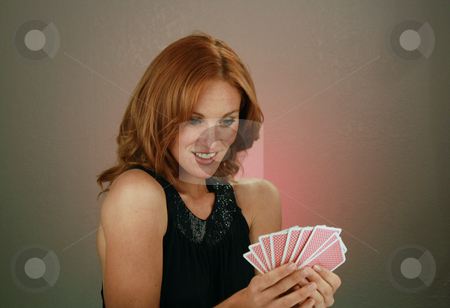 Beautiful Redhead with Playing Cards (4) stock photo, A lovely redhead model holds a hand of playing cards. by Carl Stewart
