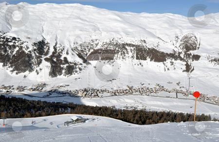 View down ski slope on chairlift station, valley and impressive mountains stock photo, View down on lower station of modern chairlift with trees and a village down in the valley plus immense mountains  in the background - shot in Livigno, Italian Alps by Frank G?