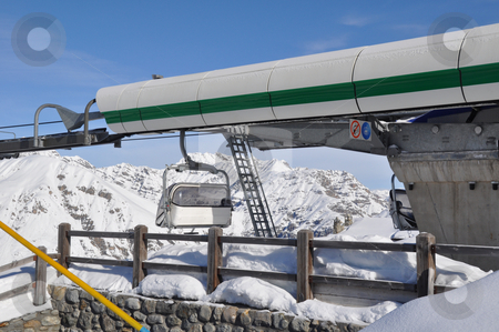 Mountain station of chairlift stock photo, Upper station of modern chairlift for 4 persons with cabin leaving and mountains in the background - shot in Livigno, Italian Alps by Frank G?