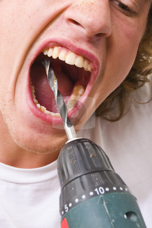 Drilling in teeth stock photo, Man with his mouth wide open, drilling in his own teeth with a drill. by Corepics VOF
