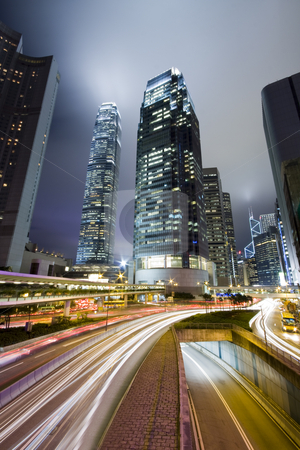 Traffic through downtown in HongKong stock photo, Hong Kong at night with highrise buildings by Keng po Leung