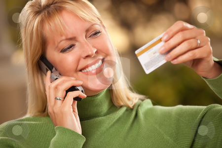 Cheerful Woman Using Her Phone with Credit Card stock photo, Cheerful Smiling Woman Using Her Phone with Credit Card in Hand. by Andy Dean