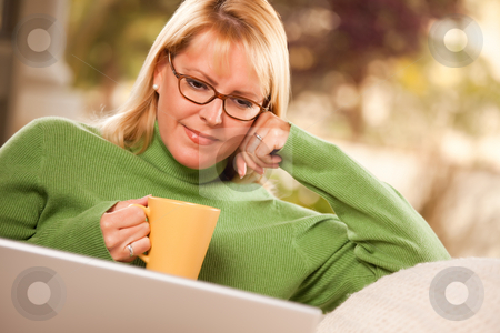 Beautiful Woman Enjoys Her Warm Drink and Laptop stock photo, Beautiful, Smiling Woman Enjoys Her Warm Drink and Laptop Relaxing Day. by Andy Dean