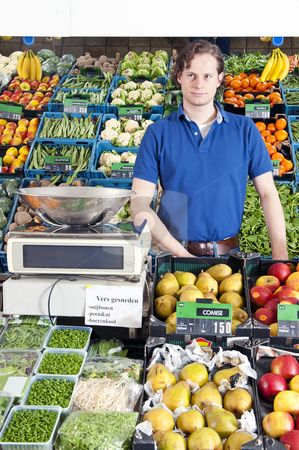 Greengrocer stock photo, A greengrocer standing behind the display counter surrounded by fresh fruit and vegetables by Corepics VOF