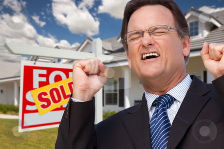 Excited Man in Front of Sold Real Estate Sign and House stock photo, Excited Man in Front of Sold Real Estate Sign and Beautiful New House. by Andy Dean
