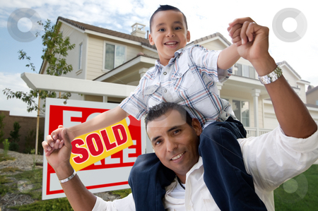 Hispanic Father and Son in Front of Their New Home stock photo, Hispanic Father and Son in Front of Their New Home with Sold Home For Sale Real Estate Sign. by Andy Dean