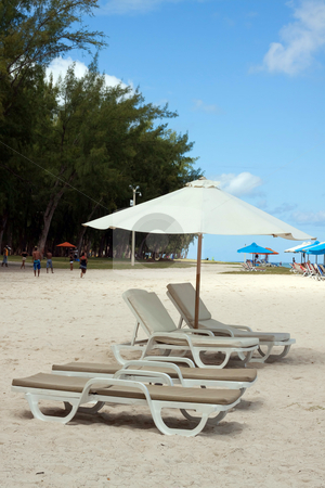 Reclining chairs on the beach stock photo, Reclining chairs under the shade of beach umbrella on the beach of Flic en Flac inmauritius by Gowtum Bachoo