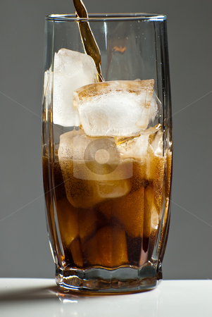 Glass of Cola stock photo, Cola being poured into a glass that is filled with ice cubes by Richard Nelson