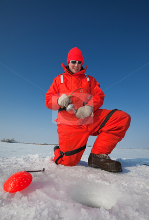Smiling ice fisherman stock photo, Smiling ice fisherman fighting a big fish through the ice by Steve Mcsweeny