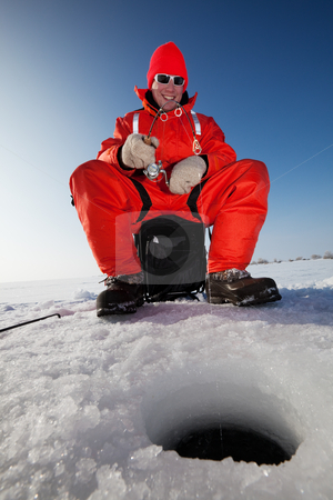 Happy fisherman  stock photo, Happy fisherman fighting a fish while ice fishing by Steve Mcsweeny