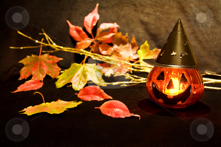 Halloween scary pumpkin  stock photo, Celebrating Halloween night with scary pumpkin candle and dead leaves. by Andreea Chiper