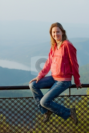 Girl stock photo, Girl sitting on a barrier in front of a beautiful landscape by P?
