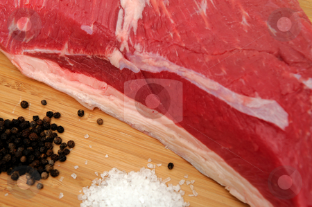 Tri Tip Roast And Species stock photo, Fresh raw tri-tip roast with fat marbled through the meat ready to roast or barbeque with sea salt, black peppercorns, herbs and garlic cloves by Lynn Bendickson