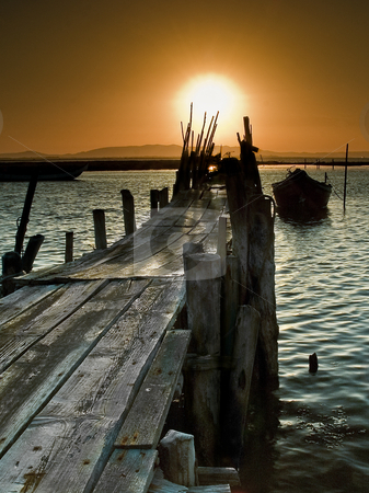 Pier stock photo, Picturesque landscape of a sunset on a coastal scene with a boat on a pier. by Homydesign