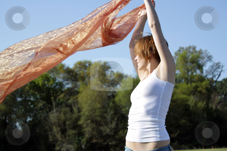 Beautiful Young Woman Outdoors (5) stock photo, A lovely young woman soaks up the morning sun outdoors with some sheer fabric. by Carl Stewart