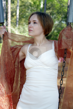 Beautiful Young Woman Outdoors (8) stock photo, A lovely young woman soaks up the morning sun outdoors with some sheer fabric. by Carl Stewart