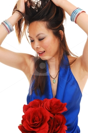 Asian girl pulling her hair. stock photo, An beautiful young Asian girl, pulling up her hair in the studio in a blue blouse with a bunch of red roses on her lap, over white Background. by Horst Petzold