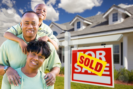 African American Family with Sold For Sale Sign and House stock photo, Happy and Attractive African American Family with Sold For Sale Real Estate Sign and House. by Andy Dean