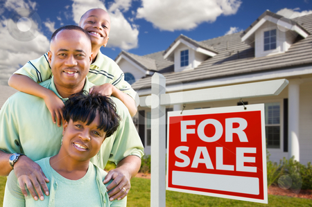 African American Family with For Sale Sign and House stock photo, Happy and Attractive African American Family with For Sale Real Estate Sign and House. by Andy Dean