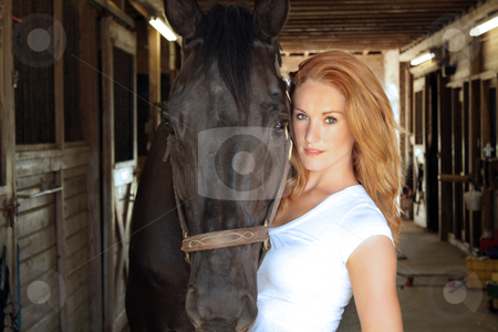 Beautiful Redhead with Her Horse (1) stock photo, A lovely young redhead with her horse inside the barn. by Carl Stewart