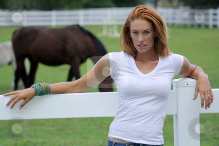 Beautiful Redhead at the Ranch (1) stock photo, A lovely young redhead in front of a white fence with horses in the background. by Carl Stewart