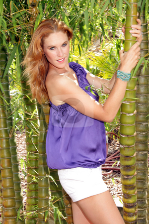 Beautiful Redhead in a Garden (6) stock photo, A lovely young redhead stands in a bamoo thicket in a lush, cultivated garden. by Carl Stewart