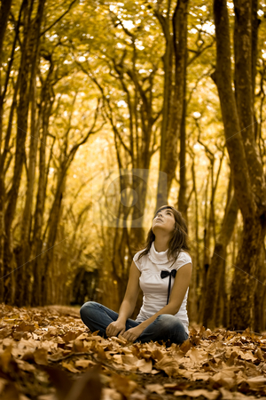 Woman in the park stock photo, Beautiful woman seated on the ground in a beautiful Autumn Park by ikostudio