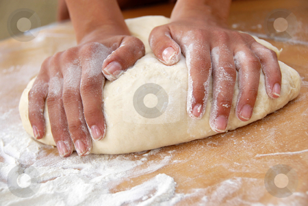 Kneading  dough stock photo, Female hands in flour closeup kneading dough on table by Julija Sapic