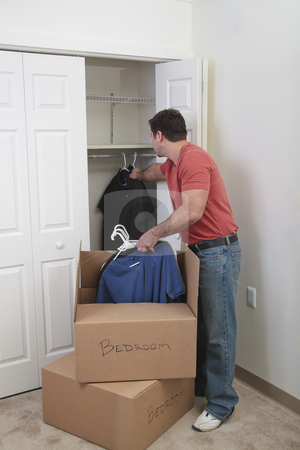 Putting the clothes away stock photo, Caucasian male hanging clothing in a closet with moving boxes by Christy Thompson
