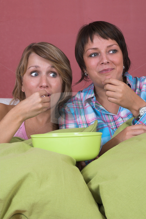 Shocking event stock photo, Two girls on the couch together watching a movie while eating popcorn and looking surprised by Simone Van den Berg