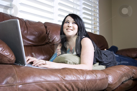 Woman on the Couch stock photo, Woman on the Couch with her Laptop by Mehmet Dilsiz