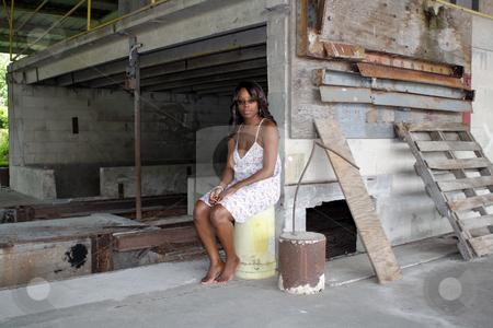 Beautifuy Black Woman at Abandoned Warehouse (22) stock photo, A lovely young black woman sits amidst the clutter of a long-abandoned warehouse. by Carl Stewart