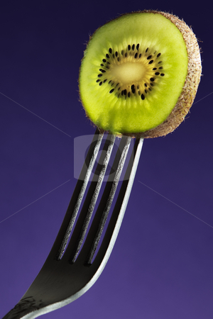The Kiwi stock photo, Kiwi fruit on a fork with sidelighting to highlight the fruit by Viv Van der Holst